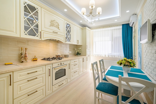 プロヴァンススタイルでデザインされたベージュ、白、シアンの現代的なクラシックキッチンのクローズアップ、すべての家具は開いたドアと引き出し付き