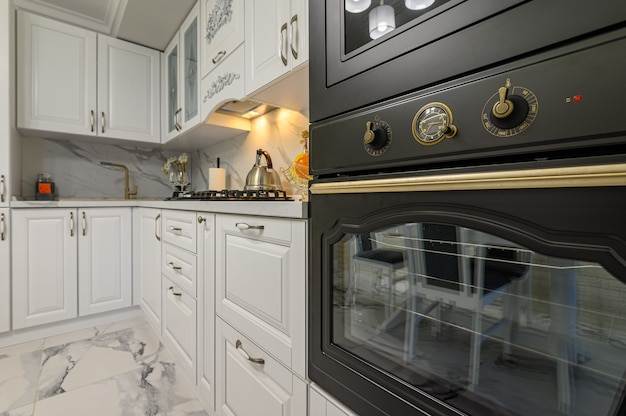 木製の家具や電化製品を備えた白いモダンなキッチンインテリアの電気オーブンとwicrowaveオーブンのクローズアップ、オーブンに焦点を当てる