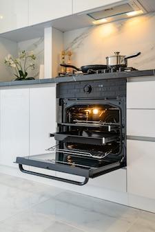 Крупным планом, чтобы открыть дверь духовки на белой современной классической кухне