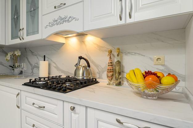 Крупным планом белый уютный современный классический интерьер кухни с деревянной мебелью и техникой, вид спереди