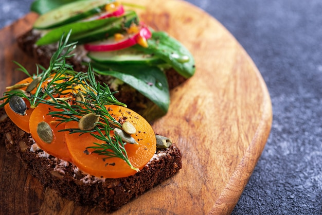Тост крупным планом с творогом и желтыми помидорами, тыквенными семечками, зеленью на деревянной доске на сером фоне, концепция здоровой вегетарианской закуски