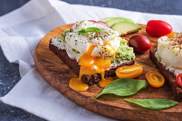 Closeup toast with poached egg, cottage cheese, avocado and vegetables on wooden board on white kitchen towel, healthy rural breakfast concept