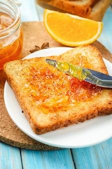 Closeup toasts with orange jam on blue