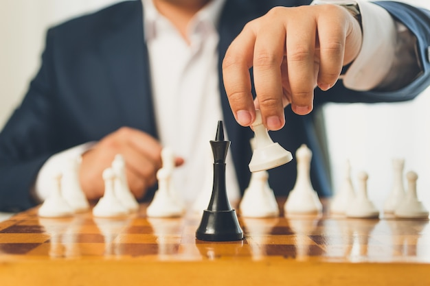 Closeup toned businessman making move with white pawn on chess board