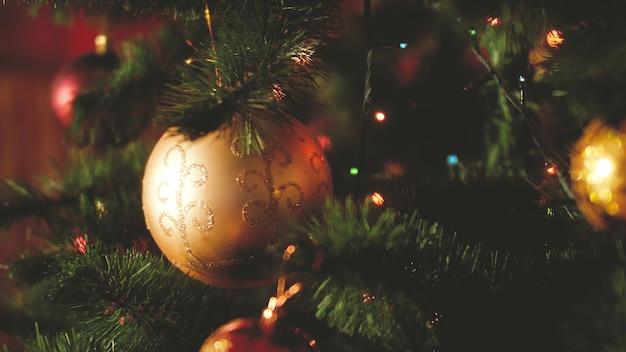 Крупным планом тонированные кадры с шарами, гирляндами и огнями, висящими на рождественской елке в канун рождества. идеальный снимок для зимних праздников и торжеств