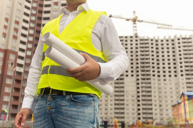 Closeup toned image of construction engineer holding blueprints