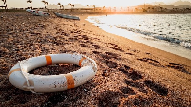 Closeup toned image of life saving ring lying on the sea baech sand. beutiful sunset over the ocean