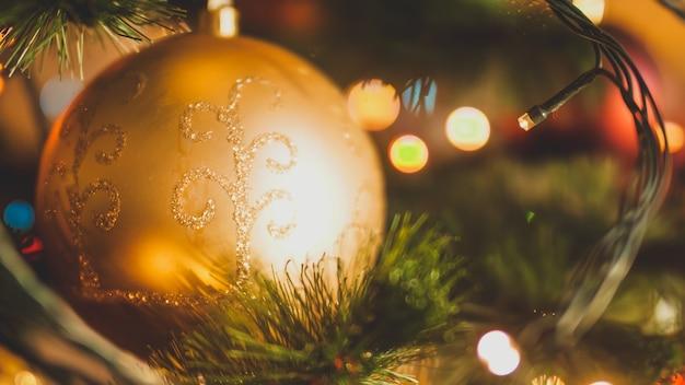 Крупным планом тонированное изображение золотого елочного шара и светящихся гирлянд на рождественской елке