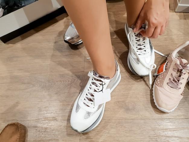 Крупным планом тонированное изображение молодой женщины, примеряющей новые кроссовки, делая покупки
