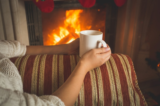 Closeup toned image of woman sitting on sofa at fireplace and holding cup of tea