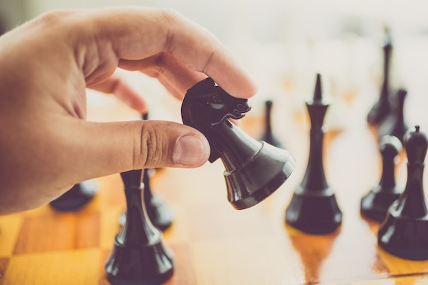 Closeup toned man making move with black horse at chess game