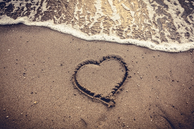 Closeup toned photo of heart drawn on sand sea beach