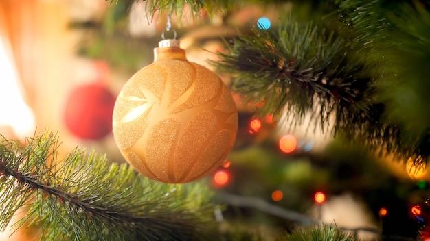 Тонированное фото крупным планом красивой растягивающейся рождественской елки, висящей на ветке на фоне солнечных лучей, сияющих через большое окно