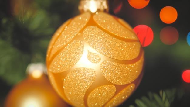 輝く光の花輪に対してクリスマスツリーの枝にぶら下がっている黄金のつまらないもののクローズアップトーンの写真。冬の休日やお祝いに最適な背景