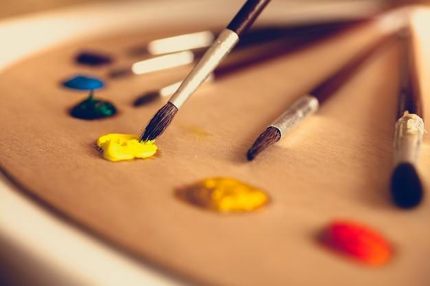 油絵の具に浸したパレットの上に横たわる絵筆のトーンのクローズ アップ写真