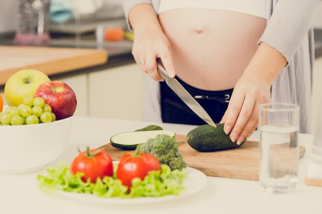 キッチンでサラダを作る妊娠中の女性のクローズ アップ トーンの写真