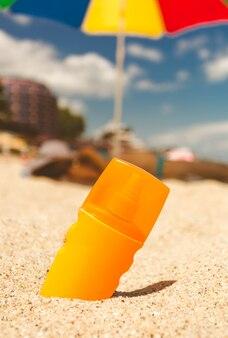 晴れた日の砂浜で日焼け止めローションのクローズ アップ トーンの写真