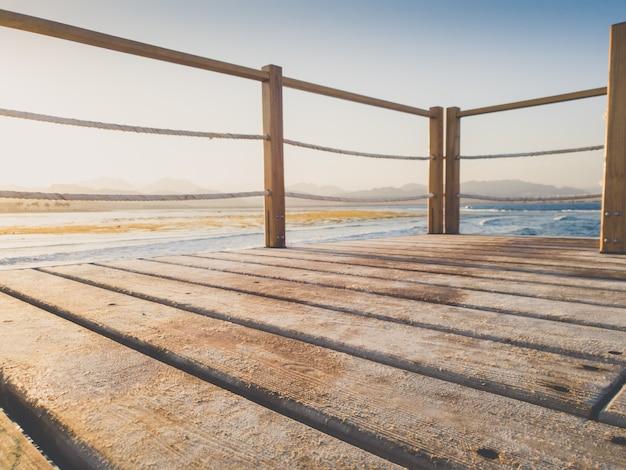 Фото тонированное крупным планом деревянного моста в море. идеально подходит для вставки вашего изображения или размещения товара. место для текста. копировать пространство