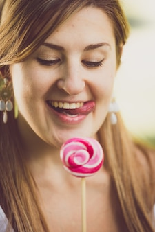 Closeup toned portrait of cute funny woman licking her lips at lollipop