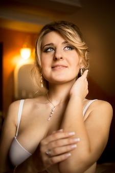 Closeup toned portrait of elegant bride in lingerie posing at hotel room