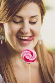 롤리팝에서 그녀의 입술을 핥는 귀여운 재미있는 여자의 근접 촬영 톤된 초상화