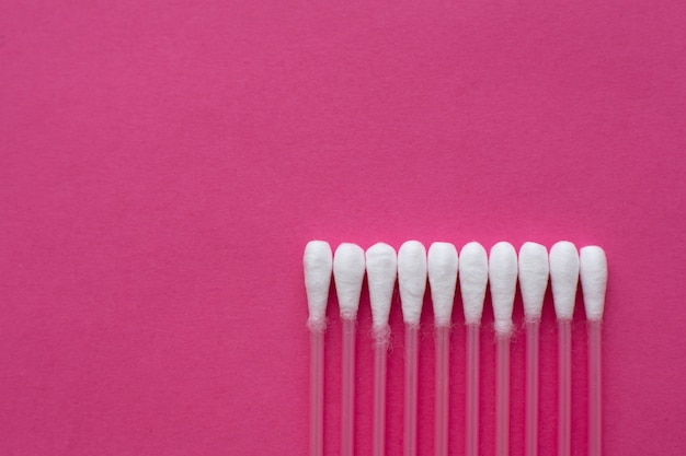 Closeup top view on cotton buds laid in a horizontal line on pink background
