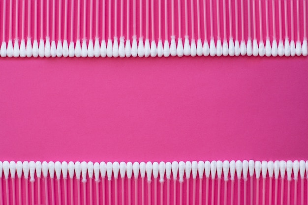Closeup top view on cotton buds laid in a two horizontal line on pink background