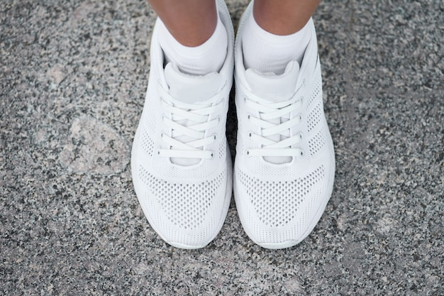 Closeup top view of female legs in stylish white sneakers. active woman on a training. ready to start.