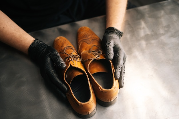 Closeup top view of hands of shoemaker shoemaker in black gloves holding old worn light brown leathe...
