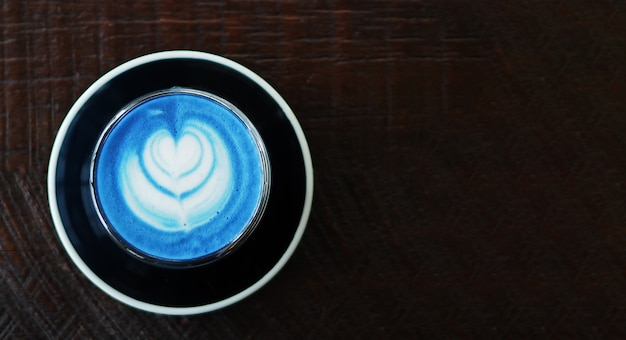 Closeup top view of hot butterfly pea latte on dark wooden table