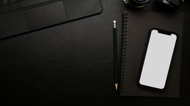 Closeup top view modern dark study table smartphone screen mockup on black surface
