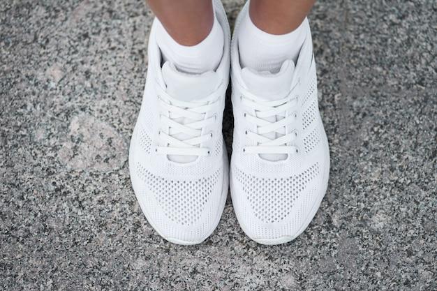 スタイリッシュな白いスニーカーで女性の足のクローズアップ平面図。トレーニングでアクティブな女性。開始する準備ができました。