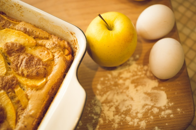 Крупным планом вид сверху пирога и свежих яблок на деревянной доске