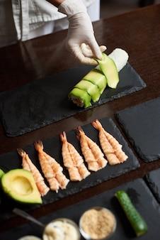 Крупным планом вид сверху процесса приготовления ролл суши в
