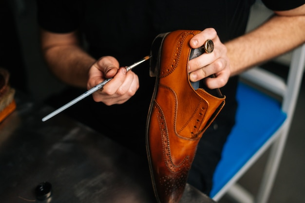 Closeup top view of shoemaker painting heel and sole of light brown leather shoes with brush during ...
