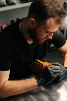 Closeup top view of shoemaker wearing black latex gloves cleaning old light brown leather shoes with...
