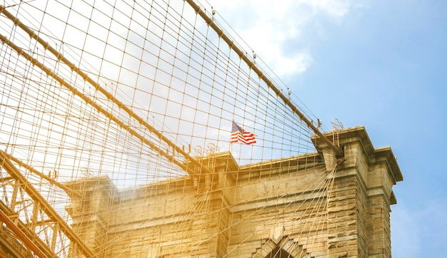 Closeup of towers and american flag over brooklyn bridge in new york city