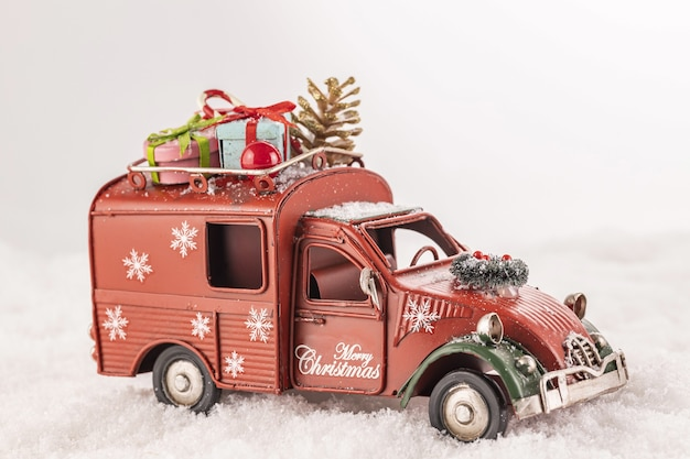 Closeup of a toy car with christmas ornaments on it on artificial snow against a white background