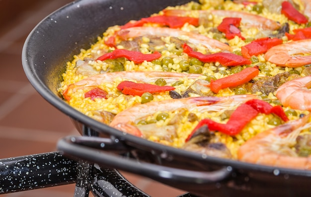 Closeup of traditional spanish paella cooked in a pan, with yellow rice and seafood