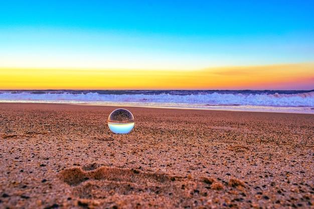 Primo piano di una palla trasparente sulla sabbia circondata dal mare durante il tramonto la sera