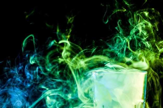 A closeup transparent glass filled with a wig from a green vape smokes and stands on a black isolate
