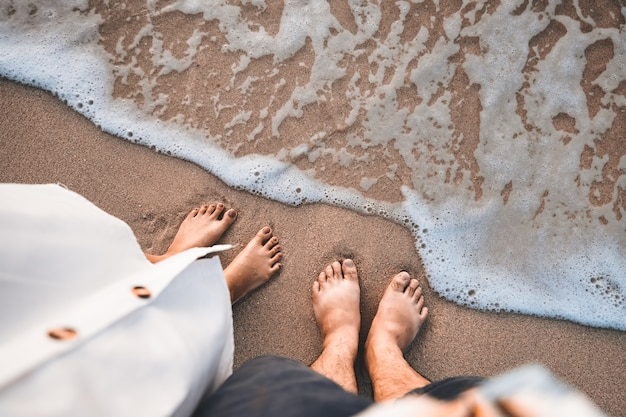 Closeup traveler man and woman foot of relaxing on beach with sea wave in summer, holiday travel vacation concept
