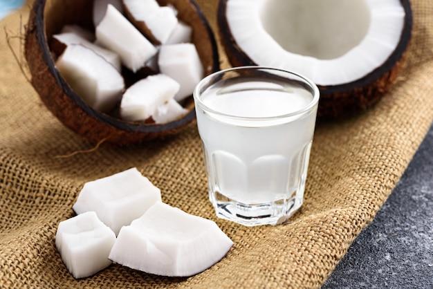 灰色の背景の上のキャンバス生地のガラスのクローズアップトレンディなさわやかなココナッツ水