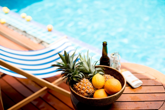 Closeup of tropical fruits in wooden basket by the poolside