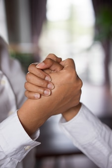 Closeup of two business women clasping hands.