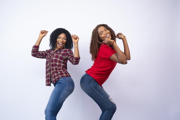 Primo piano di due giovani donne di colore eccitate che si sentono felici e ballano, davanti a uno sfondo bianco