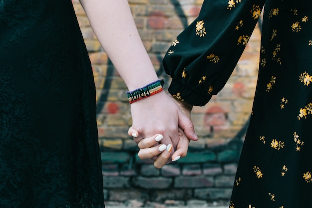 Closeup of two female lgbt gay couple holding hands
