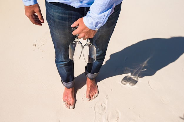 Closeup of two glasses in hand at man walking barefoot on white beach