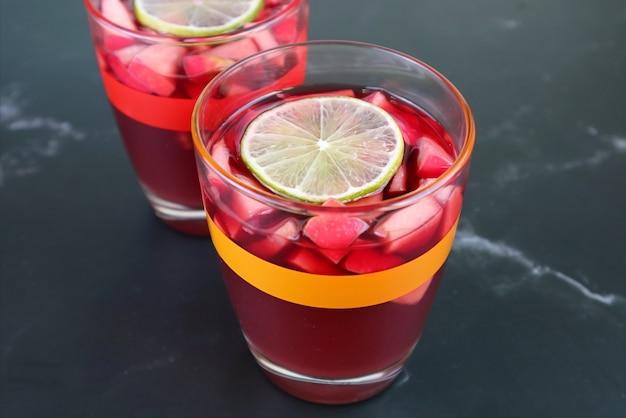 クローズアップ黒のテーブルで隔離の冷やした赤ワインサングリアの2つのグラス
