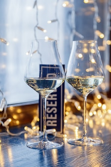 Closeup of two glasses of white wine in transparent crystal glasses and light garlands